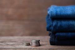 Jeans stacked with coins on a wooden background. Jeans stacked on a wooden background stock photo