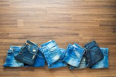 Jeans stacked on a wooden background Stock Photos