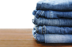 Jeans stacked on a wooden Stock Images