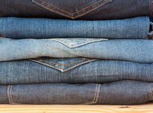 Jeans staplar, bakgrundsmodejeans Arkivfoto