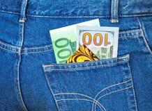 Jeans stoppa i fickan med hundra euro, hundra amerikan gör Royaltyfri Foto