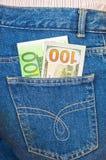 Jeans stoppa i fickan med hundra euro och hundra amerikan Royaltyfria Bilder