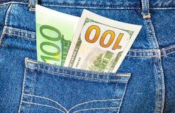 Jeans stoppa i fickan med hundra euro och hundra amerikan Arkivbild