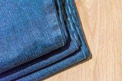 Jeans store close up. Jeans stacked on a wooden background stock image