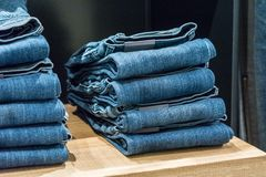 Jeans store close up. Jeans stacked on a wooden background royalty free stock photography