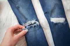 Jeans stracciati blu in una mano femminile dettaglio concetto alla moda Fotografia Stock