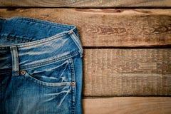 Jeans su una tavola di legno Fotografie Stock Libere da Diritti