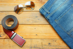 Jeans, sunglasses and leather belt on the wooden vintage Royalty Free Stock Photo