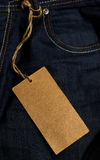 Jeans tag. Blank brown tag with rope attached to blue jeans. Can see front pocket of the jeans Stock Photo