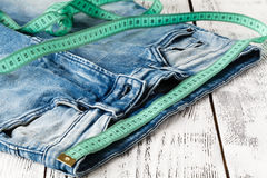 Jeans and tape measure. On wooden table Royalty Free Stock Photo