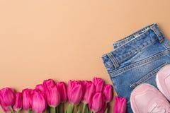 Jeans, tennisschoenen en roze tulpen Vlak leg Het concept van de manierlente Vrije ruimte De ruimte van het exemplaar stock foto's