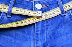 Jeans und messende Bandnahaufnahme, Konzept des gesunden Lebensstils und verlierendes Gewicht stockbilder