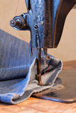 Jeans and a vintage sewing machine Stock Image