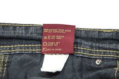 Jeans Wash Care Instructions. Washing and dry-cleaning instructions for Jeans. The cotton tag attached with cloth stock photo