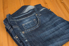 Jeans on wooden background. Dark blue jeans on wooden background Royalty Free Stock Photos