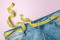 Jeans and yellow measuring tape instead of belt on pink background. Concept of weight loss, diet, detox. Thin waist royalty free stock photos