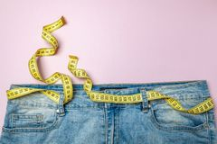 Jeans and yellow measuring tape instead of belt on pink background. Concept of weight loss, diet, detox, thin waist. Copy space for text royalty free stock photography