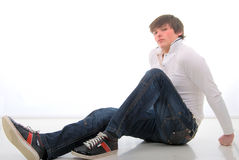 Jeans Young Mann Sitting On White Floor. Royalty Free Stock Photo
