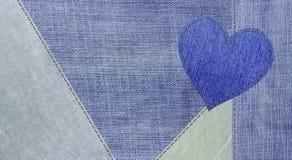 Jeansbakgrunden och en jeanshjärta arkivfoto