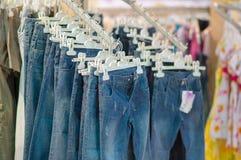 Jeanses na stojakach w dzieciaków centrum handlowym Zdjęcia Royalty Free