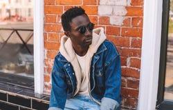 Jeansjacke des afrikanischen Mannes des Modeporträts tragende, die auf Stadtstraße über strukturierter Wand des Ziegelsteines sit stockfotografie