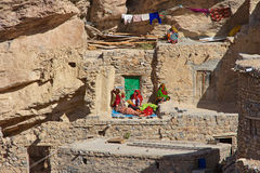 Jebel Akhdar Cliff Hamlet. Omani women relaxing outside a traditional stone house in a small cliff hamlet near Sroot, in the Jebel Akhdar mountains, Sultanate of royalty free stock images
