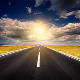 Jechać na pustej nowej asfaltowej drodze przy zmierzchem zdjęcia royalty free
