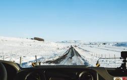 Jechać na wiejskiej drodze w zimie Patrzejący przez samochodu przodu windscreen, marznąca droga z śniegiem zakrywał wewnątrz i ja Zdjęcie Stock