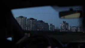 Jechać w mieście w wieczór Wysocy budynki mieszkaniowi na jeden stronie droga zbiory wideo