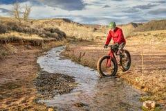 Jechać grubego rower przez strumienia Zdjęcia Stock