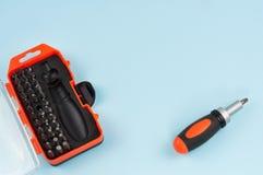 Jeden śrubokręt z rękojeścią czarny i pomarańczowy kolor blisko ustawia metali kawałki w pudełku na błękitnym tle zdjęcie stock