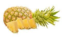 Jeden ananasowa owoc z plasterkami odizolowywającymi na bielu Zdjęcia Stock