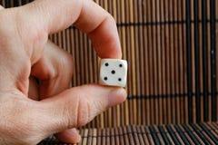Jeden biały klingeryt dices w mężczyzna ` s ręce na brown drewnianym stołowym tle Sześć stron sześcianów z czarnymi kropkami Licz Fotografia Royalty Free