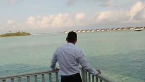 Jeden biznesmen w oficjalnej kostium pozyci na balkonie jego willa bungalow, patrzeć piękna błękitna laguna i zbiory