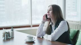 Jeden biznesowa kobieta siedzi w kawiarni, ono uśmiecha się i opowiada na telefonie zbiory wideo