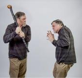 Jeden bliźniaczy senior wokoło uderzać inny z jego trzciną fotografia stock