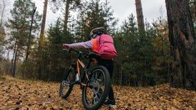 Jeden caucasian dzieci chodzą z rowerem w jesień parku Mała dziewczynka chodzi czarnego pomarańczowego cykl w lasowym dzieciaku i zdjęcia stock