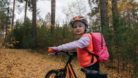 Jeden caucasian dzieci chodzą z rowerem w jesień parku Mała dziewczynka chodzi czarnego pomarańczowego cykl w lasowym dzieciaku i fotografia royalty free