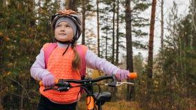Jeden caucasian dzieci chodzą z rowerem w jesień parku Mała dziewczynka chodzi czarnego pomarańczowego cykl w lasowym dzieciaku i zdjęcie stock