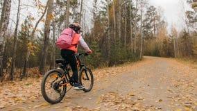 Jeden caucasian dzieci przejażdżek roweru droga w jesień parku Mała dziewczynka jedzie czarnego pomarańczowego cykl w lasowym dzi zdjęcia stock