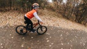 Jeden caucasian dzieci przejażdżek roweru droga w jesień parku Mała dziewczynka jedzie czarnego pomarańczowego cykl w lasowym dzi obraz stock