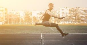 Jeden caucasian samiec w skoku nad barier? biega? na stadium Zawody atletyczni biegacz w sporta mundurze w locie energiczny fotografia stock