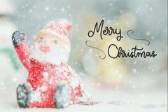 Jeden ceramiczny Santa Claus Wesoło bożych narodzeń tekst na opadu śniegu tle fotografia royalty free