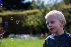 Jeden chłopiec dmucha mydlanych bąble w ogródzie na letnim dniu Obrazy Stock