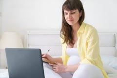 Jeden ciężarna europejska kobieta pracuje od ona do domu podczas gdy siedzi na białym łóżku przy dnia czasem Obrazy Royalty Free