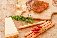 Jeden częsciowo ciący kawałek i plasterki leczący ser wieprzowiny i parmesan zdjęcia royalty free