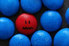 Jeden czerwona kropla z malującą smutną twarzą wśród błękita ones Obraz Stock
