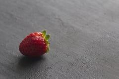 Jeden czerwona pi?kna truskawka w g?r? na czarnym zmroku betonu tle, minimalista Boczny widok, kopii przestrze? dla tw?j teksta M zdjęcia stock