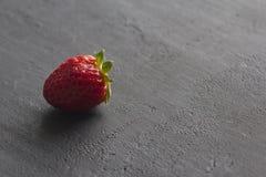 Jeden czerwona pi?kna truskawka w g?r? na czarnym zmroku betonu tle, minimalista Boczny widok, kopii przestrze? dla tw?j teksta M obraz royalty free