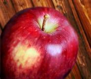 Jeden czerwony jabłko na drewno stole Obrazy Royalty Free